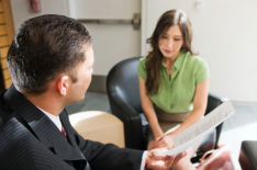 The photo shows a job interview with a recruiter and a job applicant discussing job interview questions